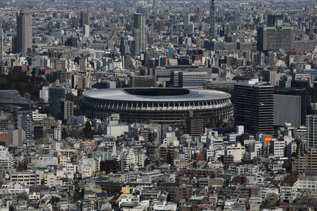 FILE - In this March 3, 2020, file photo, the New National Stadium, a venue for the opening and closing ceremonies at the Tokyo 2020 Olympics, is seen from Shibuya Sky observation deck in Tokyo. The tentacles of cancelling the Tokyo Olympics — or postponing or staging it in empty venues — would reach into every corner of the globe, much like the spreading virus that now imperils the opening ceremony on July 24. (AP Photo/Jae C. Hong, File)