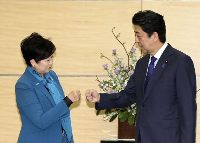 "Tokyo Gov. Yuriko Koike, left, and Japan's Prime Minister Shinzo Abe greet with fist-bump prior to their meeting at the prime minister's office in Tokyo, Thursday, March 12, 2020.  Tokyo Governor Koike acknowledges that the World Health Organization's declaration that the coronavirus is a pandemic could impact the Tokyo Olympics. But she says ""I believe cancellation is impossible."" (Toshiyuki Matsumoto/Kyodo News via AP)"