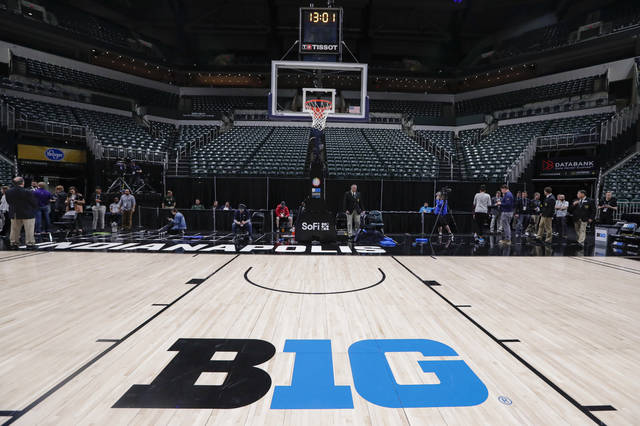 The seating area at Bankers Life Fieldhouse is empty as media and staff mill about, Thursday, March 12, 2020, in Indianapolis, after the Big Ten Conference announced that remainder of the men's NCAA college basketball games tournament was cancelled. (AP Photo/Michael Conroy)