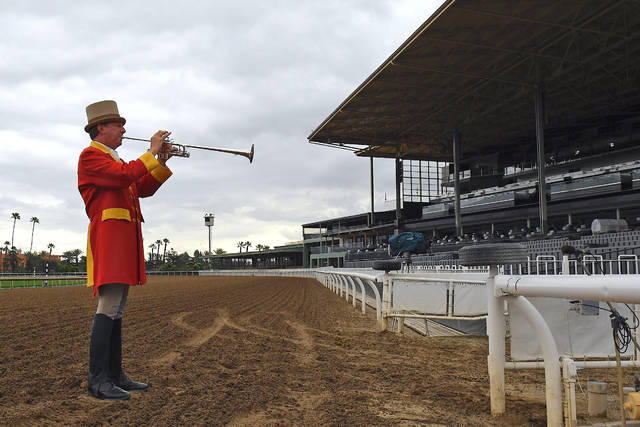 """Bugler Jay Cohen plays """"First Call"""" as he calls the riders to post for the first race at Santa Anita Park to empty stands Saturday, March 14, 2020, in Arcadia, Calif. While most of the sports world is idled by the coronavirus pandemic, horse racing runs on. (AP Photo/Mark J. Terrill)"""