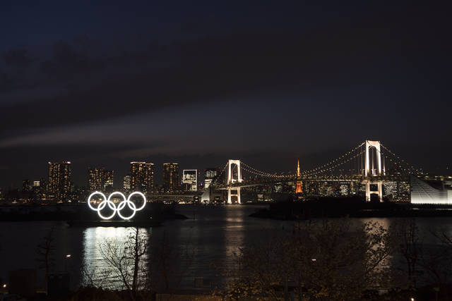 The Olympic rings float in the water near the Rainbow Bridge in the Odaiba section of Tokyo, Monday, March 23, 2020. The Tokyo Olympics are going to happen — but almost surely in 2021 rather than in four months as planned. (AP Photo/Jae C. Hong)