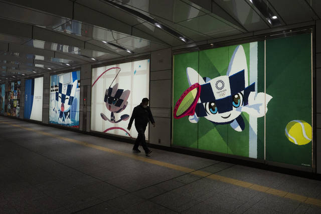 """A man walks past large displays promoting the Tokyo 2020 Olympics in Tokyo, Tuesday, March 24, 2020. IOC President Thomas Bach has agreed """"100%"""" to a proposal of postponing the Tokyo Olympics for about one year until 2021 because of the coronavirus outbreak, Japanese Prime Minister Shinzo Abe said Tuesday. (AP Photo/Jae C. Hong)"""