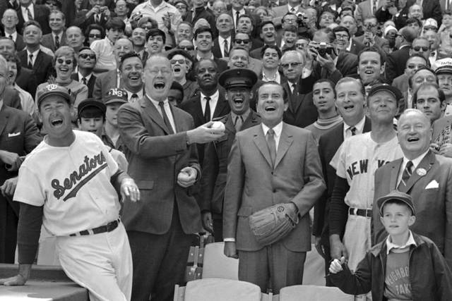 FILE - In this April 7, 1969, file photo, President Richard Nixon and Baseball Commissioner Bowie Kuhn, center-left, join Washington Senators manager Ted Williams, left, in a round of laughter before the chief executive tossed out the first ball in an opening day baseball game at RFK Stadium in Washington. (AP Photo/File)