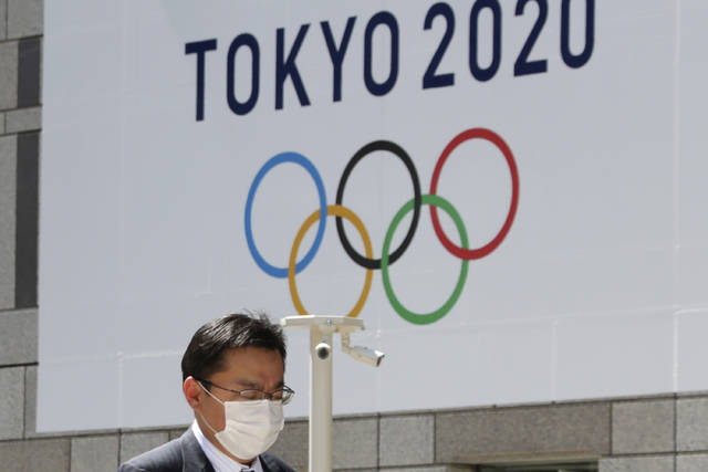 FILE - In this Wednesday, March 25, 2020, file photo, a man walks in front of a Tokyo Olympics logo at the Tokyo metropolitan government headquarters. The postponement of the Tokyo Games has catapulted the sports organizations that make up the backbone of the U.S. Olympic team into crisis. (AP Photo/Koji Sasahara, File)