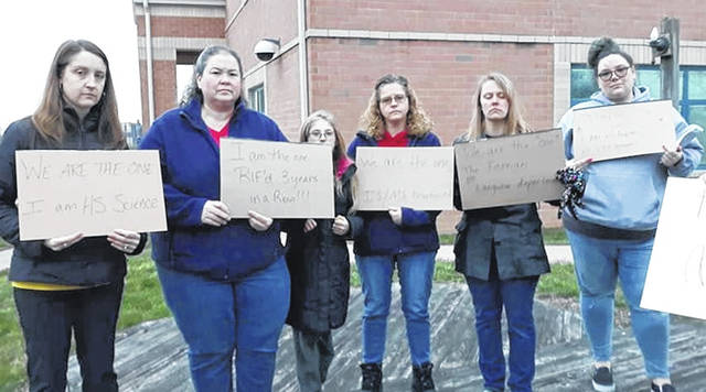 Outside Blanchester Local Schools Monday evening holding signs are, from left: Sara Estrada, high school science teacher; Jennifer Chaplin, aide; Joanna Powell IS/MS receptionist; Robin Fille, foreign language teacher; and Torie Mollet, high school English teacher. Their jobs are affected by the cuts approved for 2020-21.