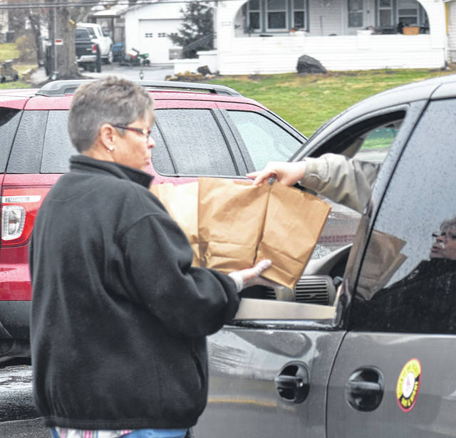 Denver Place Elementary librarian Deborah Murphy hands lunches to arriving families on Wednesday.