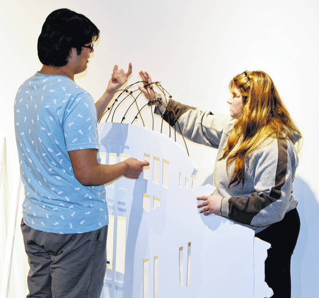 "Jorge Herrera, a senior history major, and Mikaela Prescott, a junior history major, work on the ""Gifts of Peace: Historical Artifacts as Reconciliation and Healing"" exhibit. They are putting finishing touches on the Atomic Dome, a monument in Hiroshima depicting the former city hall, which stood at the epicenter of the atomic bombing nearly 75 years ago."
