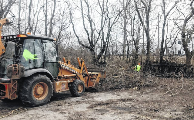 City of Wilmington workers clear out overgrown brush and clean-up discarded trash, some from past encampments, in the area by the creek and railroad tracks at the corner of E. Main St. and Grant St. on Monday afternoon.