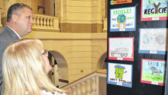 In the left foreground are Clinton County Commissioner Brenda Woods and Commissioner Mike McCarty pondering their picture picks in the annual Clinton County Solid Waste District's Earth Day poster contest. Local student-artists grades K through 5 take part in the activity.