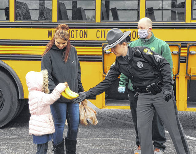 Sgt. Brittany Noah with the Wilmington post of the Ohio State Highway Patrol gives bananas to a girl on Tuesday, in a project where patrol troopers and dispatchers are assisting Wilmington City Schools (WCS) with meal distribution for students who are learning remotely at home during the COVID-19 health emergency. Please note that student lunches are available for <em>every</em> Wilmington City Schools student, regardless of income or age. WCS has six pickup locations for the meals within the school district. In the photo behind Sgt. Noah is Wilmington High School theater teacher Ken Lydy.