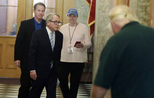 Ohio Gov. Mike DeWine, wearing glasses, and Lt. Gov. Jon Husted, background left, prepare to meet with members of the Food and Drug Administration as they walk to their daily coronavirus news conference, Sunday, March 29, 2020, at the Ohio Statehouse in Columbus, Ohio. Walking with them is DeWine's communications director, Lisa Peterson. (Doral Chenoweth/The Columbus Dispatch via AP)