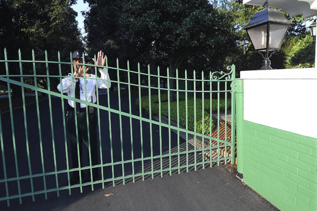 A guard at the main gate to Augusta National Golf Club warns away visitors on what would have been the first practice round for the Masters on Monday, April 6, 2020, in Augusta, Ga. Augusta National Golf Club is all locked up. Popular restaurants are shuttered, offering only curbside service if they are open at all. Washington Road, which should've been teeming with cars and commerce and humanity, is desolate instead.. (Curtis Compton/Atlanta Journal-Constitution via AP)