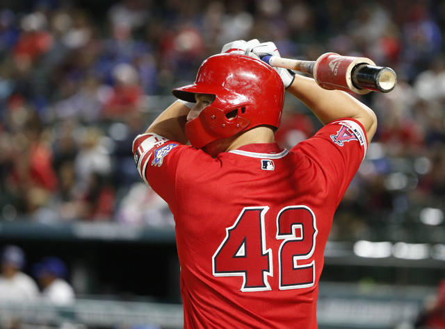 FILE - In this April 15, 2019, file photo, Los Angeles Angels designated hitter Mike Trout prepares to bat against the Los Angeles Angels during the eighth inning of a baseball game in Arlington, Texas. With the national sports calendar on hold because of the coronavirus, there will be no games Wednesday, April 15, 2020, on Jackie Robinson Day, when every person in uniform wears Robinson's retired No. 42. MLB games and NBA playoffs were among sporting events that had been scheduled this week. (AP Photo/Michael Ainsworth, File)
