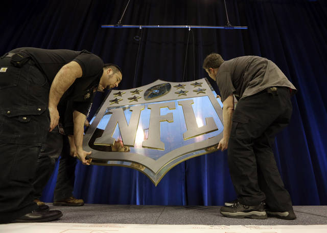 """FILE - In this Feb. 4, 2016, file photo, workers hang an NFL shield on the main stage before a news conference in San Francisco. The NFL and its players union have agreed to conduct """"virtual"""" offseason workout programs until every team is permitted to open its facilities. Teams can hold classroom instruction, workouts and non-football educational programs using online platforms, according to a memo sent to the teams that was obtained by The Associated Press. (AP Photo/David J. Phillip, File)"""
