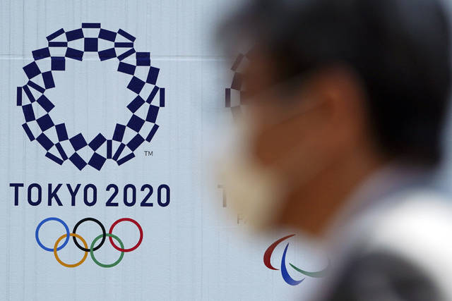 """FILE - In this April 2, 2020, file photo, a man wearing a face mask walks near the logo of the Tokyo 2020 Olympics, in Tokyo. Tokyo organizers said Tuesday, April 14, 2020 they have no """"B Plan"""" for again rescheduling the Olympics, which were postponed until next year by the virus pandemic. They say they are going forward under the assumption the Olympics will open on July 23, 2021. (AP Photo/Eugene Hoshiko, File)"""