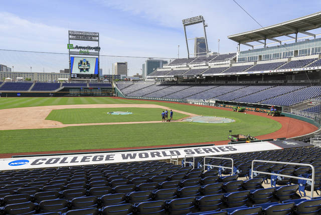 In this June 13, 2018 file photo, grounds crew prepare TD Ameritrade Park in Omaha, Neb., for the NCAA baseball College World Series. The Division I baseball championship, decided in this city of just under a half-million for the past 70 years, is among the many sporting events canceled or postponed because of the coronavirus pandemic. (AP Photo/Nati Harnik, file)
