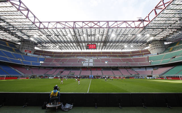 FILE - In this Sunday, March 8, 2020 filer, a view of the empty stadium during the Serie A soccer match between AC Milan and Genoa at the San Siro stadium, in Milan, Italy. While soccer leagues around Europe are still debating whether and when to resume playing, the leader of the continent's Federation of Sports Medicine Associations is calling for a detailed series of tests to clear athletes for a return to training. Maurizio Casasco, who is also president of the Italian Federation of Sports Medicine, said that guidelines recently published by his domestic federation should be extended for all of Europe -- especially if UEFA intends to resume the Champions League and Europa League anytime soon. (AP Photo/Antonio Calanni, File)