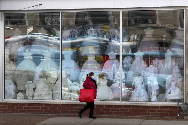 A woman wearing a protective mask walks past a closed children's clothing store in the Hispanic, Little Village in Chicago, Wednesday, April 15, 2020. The first U.S. economic indicators to capture the devastation brought on by the pandemic have begun to arrive, showing a plunge in retail sales exceeding what happened during the economic crisis a decade ago. (AP Photo/Charles Rex Arbogast)