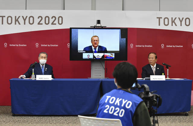 Tokyo 2020 Organizing Committee President Yoshiro Mori, left, and CEO Toshiro Muto, right, attend teleconference with International Olympic Committee member John Coates, who heads the inspection team for Tokyo Olympics, in Tokyo Thursday, April 16, 2020. Tokyo Olympic organizers and the IOC said Thursday they will cut some of the extras out of next year's postponed games, an attempt to limit what is expected to be billions of dollars in added expenses.(Kazuhiro Nogi/Pool Photo via AP)