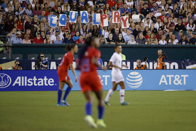 FILE - In this Aug. 29, 2019, file photo, fans hold up a sign for equal pay during the second half of an international friendly soccer match between the United States and Portugal in Philadelphia. The United States won 4-0. Last summer's Women's World Cup in France, as well as this summer's Olympics in Tokyo, and the rising emphasis on gender equity has put the spotlight on women's sports. But the coronavirus pandemic threatens to derail those gains globally. (AP Photo/Matt Slocum, File)
