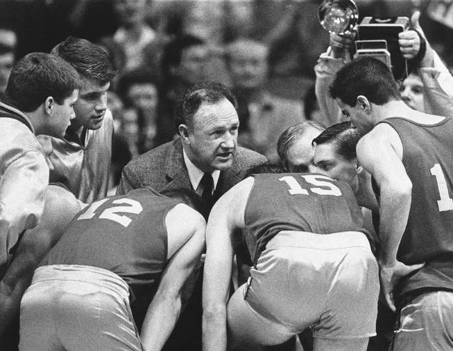 "FILE - In this Dec, 6, 1985, file photo, actor Gene Hackman gives fictional Hickory High basketball players instructions during filming of the final game of the movie ""Hoosiers"" at Hinkle Fieldhouse on the Butler University campus in Indianapolis. ""Hoosiers"" shot all the way to No. 1 in The Associated Press Top 25 of best sports movies, a one-of-a-kind poll from the news organization known for its rankings of college teams. Released in 1986 and starring Gene Hackman, ""Hoosiers"" led the tally in results released Friday, April 17, 2020, receiving 46 votes from a 70-person global panel of sports writers and editors who work for the AP.  (AP Photo/Tom Strickland, File)"
