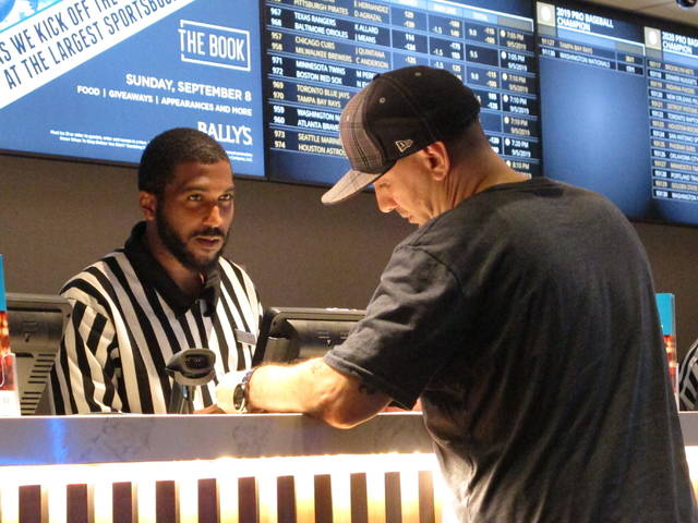 FILE - In this Sept. 5, 2019, file photo, a gambler making a sports bet at Bally's casino in Atlantic City, N.J. The NFL draft starting on Thursday, April 23, 2020, is expected to be the most heavily wagered-on draft ever, mainly because virtually all major sporting events have been postponed due to the coronavirus outbreak. (AP Photo/Wayne Parry, File)