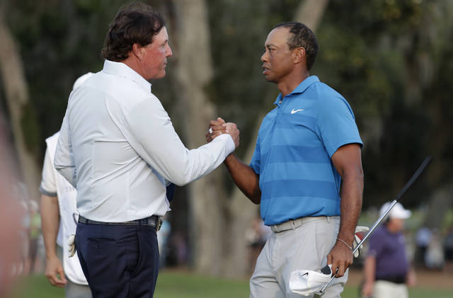 FILE - In this May 10, 2018, file photo, Phil Mickelson, left, and Tiger Woods shake hands after the first round of the Players Championship golf tournament in Ponte Vedra Beach, Fla. Woods and Mickelson are ready for a made-for-TV rematch at a time when fans are craving live action. And this time, they'll have company. Turner Sports says quarterbacks Tom Brady and Peyton Manning will join them for a two-on-two match sometime in May. Missing from the announcement were such details as when and where the match would be played, except that tournament organizers would work with government and health officials to meet safety and health standards. (AP Photo/Lynne Sladky, File)