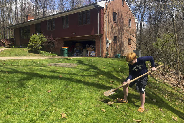 In this April 21, 2020, photo, Wyatt Anthony, 13, covers an apple core with dirt as part of his effort to grow an apple tree at the side of his front yard in Allison Park, Pa. Wyatt has not been within 50 feet of an acquaintance outside his immediate family since March 13. (AP Photo/Ted Anthony)