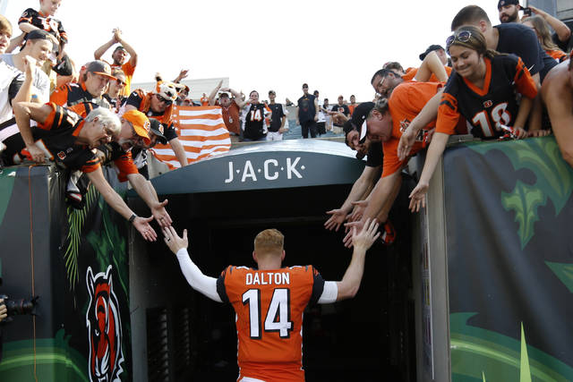 FILE - In this Oct. 7, 2018, file photo, Cincinnati Bengals quarterback Andy Dalton (14) high-fives fans as he leaves the field following an NFL football game against the Miami Dolphins in Cincinnati.  The Bengals cleared the way for Joe Burrow to lead the team by releasing quarterback Andy Dalton, who holds several of the franchise's passing records but couldn't lead the woebegone Bengals deep into the playoffs. The move Thursday, April 30, 2020, gives Dalton, who had a year left on his deal, a chance to compete for a job with another team. (AP Photo/Frank Victores, File)