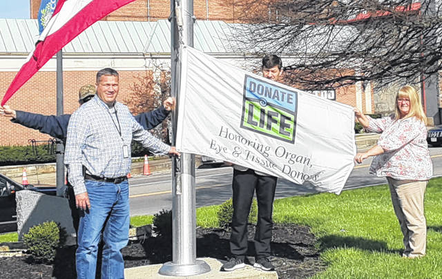 """Clinton County commissioners have proclaimed April as """"Donate Life Month"""" and held a flag-raising on the southwest corner of courthouse square for a banner that publicizes organ and tissue donation. The annual observation is spurred locally by organ donor advocates Shelby and Tom LaPine. The LaPines are the parents of organ donor Luke LaPine, who died in June 2014. In the foreground from left are Clinton County Commissioners Mike McCarty, Kerry Steed and Brenda Woods; partly visible behind McCarty and displaying the U.S. and Ohio flags is county maintenance employee Kenny Burdette."""