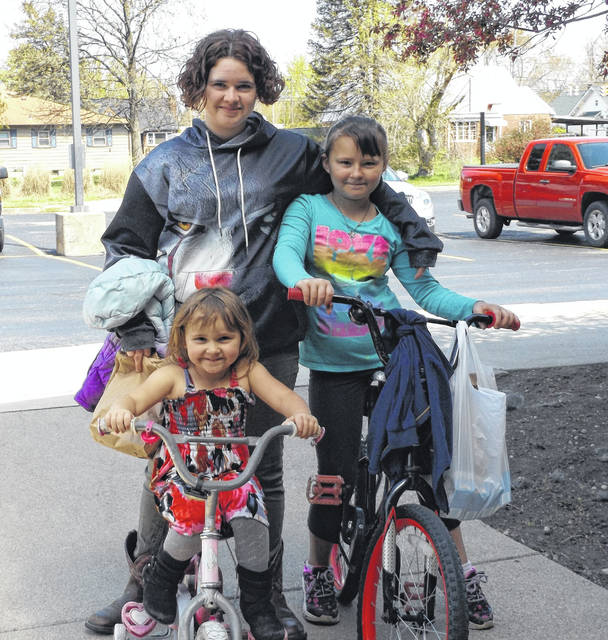 Coming to Sabina Elementary School to pick up a hot lunch Wednesday (and breakfast for Thursday) are students Hope Morrow, standing, and seated on bikes clockwise her sisters Sophie Conley and Felicity Conley.