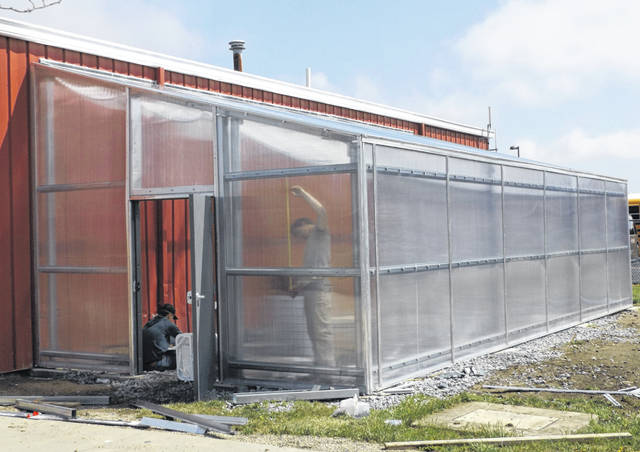 A new greenhouse on the Clinton-Massie campus is nearing completion. In 2019, the Bayer Fund awarded a $25,000 grant to the school district. Once nominated, a school district submits an application to compete for $10,000 or $25,000 grants to help fund projects that enhance their STEM (Science, Technology, Engineering, and Math) curriculum. Further, the Clinton and Warren Counties Farm Bureaus each donated $1,000 to be put toward the greenhouse interior. Ultimately, the greenhouse will be wheelchair accessible with the installation of a concrete strip through the middle of the structure's interior. The fourth wall of the greenhouse is a side wall of the red bus garage.
