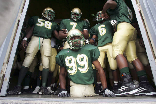 FILE - In this Sept. 15, 2005, file photo, Colonel White's Bobby Martin (99) waits with teammates at the locker room door before entering the playing field for a game against Dunbar in Dayton, Ohio. Martin, born without legs who garnered national praise while playing high school football, died in all-terrain vehicle crash on Tuesday, April 28, 2020. He was 32. The former high school football star was born without legs but gained national praise in 2005 when he played with the school's team even after being told at halftime that he could not finish the game because he was violating a rule that required players to wear shoes, thigh pads and knee pads. (Jim Witmer/Dayton Daily News via AP)