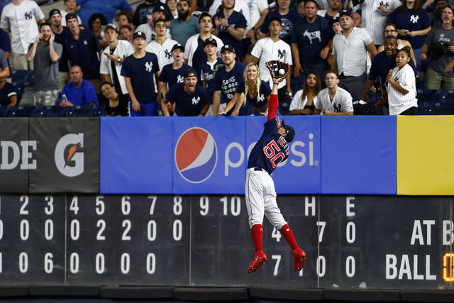 FILE - In this Sunday, Aug. 4, 2019, file photo, Boston Red Sox right fielder Mookie Betts makes a leaping catch on a ball hit by New York Yankees' DJ LeMahieu during the eighth inning of a baseball game in New York. With the sports calendar still mostly on hold because of the coronavirus pandemic, The Associated Press takes a look at some of the live sporting events that would have taken place the week of May 4-10, 2020, including the season's first meeting between the Red Sox and Yankees, in The Bronx. (AP Photo/Adam Hunger, File)