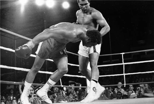 """FILE - In this Oct. 30, 1974, file photo, challenger Muhammad Ali, top, watches as defending world champion George Foreman goes down to the canvas in the eighth round of their WBA/WBC championship match in Kinshasa, Zaire. The 1996 film """"When We Were Kings"""" is a documentary of the bout known as the """"Rumble In The Jungle"""" between Ali and Foreman. The fight was a cultural milestone that ran far deeper than boxing. (AP Photo/File)"""