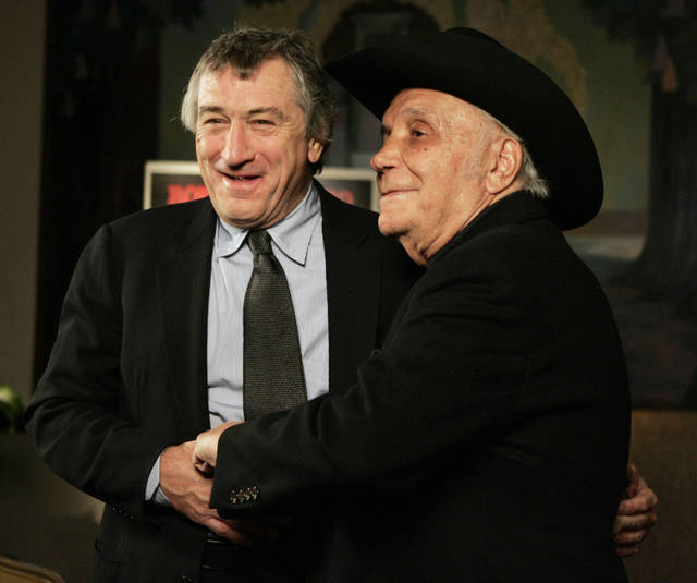 """FILE - In this Jan. 27, 2005, file photo, Robert De Niro, left, and boxer Jake LaMotta stand for photographers before watching a 25th anniversary screening of the movie """"Raging Bull,"""" in New York. """"Raging Bull,"""" about the life of Jake Lamotta, was No. 7 in The Associated Press' Top 25 favorite sports movies poll. (AP Photo/Julie Jacobson, File)"""