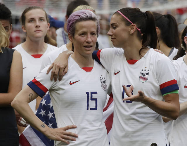 FILE - In this July 7, 2019, file photo, United States' Megan Rapinoe, left, talks to her teammate Alex Morgan, right, after winning the Women's World Cup final soccer match against Netherlands at the Stade de Lyon in Decines, outside Lyon, France. Players for the U.S. women's national team may have been dealt a blow by a judge's ruling in their gender discrimination case against U.S. Soccer, but the case is far from over. On Friday a federal judge threw out the players' unequal pay in a surprising loss for the defending World Cup champions. But the judge allowed aspects of their allegations of discriminatory working conditions to go to trial. (AP Photo/Alessandra Tarantino, File)