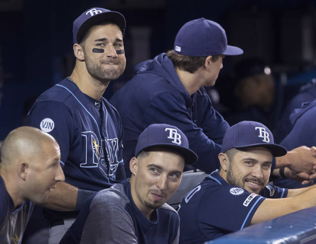 FILE - In this Sept. 28, 2019, file photo, Tampa Bay Rays' Kevin Kiermaier, top left, relaxes in the dugout with teammates in the fourth inning of a baseball game against the Toronto Blue Jays in Toronto. Major League Baseball's average salary as opening day approached remained virtually flat at around $4.4 million for the fifth straight season, according to a study of contracts by The Associated Press. (Fred Thornhill/The Canadian Press via AP, File)