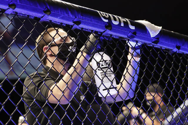 A worker wipes down areas of the octagon between bouts at a UFC 249 mixed martial arts event Saturday, May 9, 2020, in Jacksonville, Fla. (AP Photo/John Raoux)