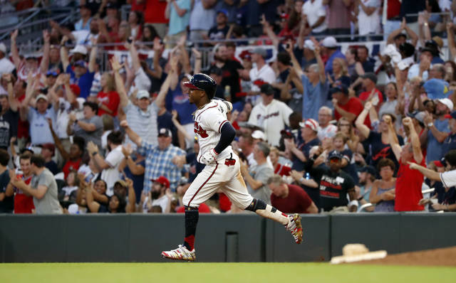 FILE - In this July 4, 2019, file photo, Atlanta Braves' Ozzie Albies rounds first base after hitting a three-run home run during the third inning of the team's baseball game against the Philadelphia Phillies in Atlanta. Major League Baseball owners gave the go-ahead Monday, May 11, 2020, to making a proposal to the players' union that could lead to the coronavirus-delayed season starting around the Fourth of July weekend in ballparks without fans, a plan that envisioned expanding the designated hitter to the National League for 2020. (AP Photo/John Bazemore, File)