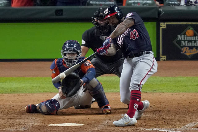 """FILE - In this Oct. 30, 2019, file photo, Washington Nationals' Howie Kendrick hits a two-run home run against the Houston Astros during the seventh inning of Game 7 of the baseball World Series in Houston. To many National League fans, the scribble of """"DH"""" on the lineup card sullies the whole stadium. To lots of American League fans, the sight of a pitcher touching a Louisville Slugger is a total affront to the diamond. No matter, that's part of the proposal MLB owners are making to the players -- a full-time DH in the National League. This year only. (AP Photo/Eric Gay, File)"""