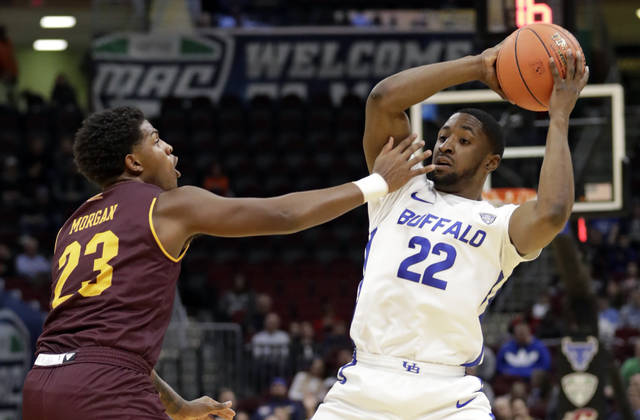 FILE - In this March 15, 2019, file photo, Buffalo's Dontay Caruthers (22) looks to pass as Central Michigan's Dallas Morgan (23) defends during the first half of an NCAA college basketball game in the semifinals of the Mid-American Conference men's tournament in Cleveland. The Mid-American Conference is eliminating postseason tournaments in eight sports, including baseball and softball, and men's and women's basketball are among nine sports that will have postseasons scaled back. The MAC's announced the cost-cutting move Tuesday in response to the financial crisis being brought on by the coronavirus pandemic. (AP Photo/Tony Dejak, File)