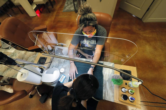 Customer Gabi Bustillo gets a manicure through new plexiglass partitions at Luxurie Nail Spa in Harahan, La., Friday, May 15, 2020. Once a hot spot for coronavirus infections, Louisiana is officially easing up Friday on economically devastating business closures and public gathering restrictions that Gov. John Bel Edwards credits with slowing the spread of the virus. With certain limitations — and excluding New Orleans, which doesn't begin easing restrictions until Saturday — Louisiana residents can eat inside restaurants again. (AP Photo/Gerald Herbert)