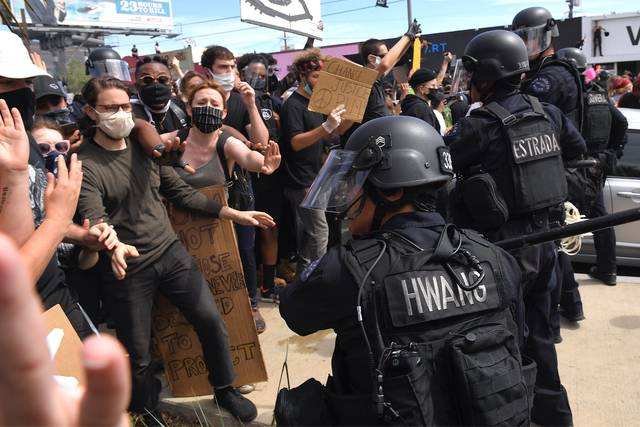 A Los Angeles police officer threatens protesters during a protest over the death of George Floyd Saturday, May 30, 2020, in Los Angeles. Protests across the country have escalated over the death of George Floyd who died after being restrained by Minneapolis police officers on Memorial Day, May 25. (AP Photo/Mark J. Terrill)