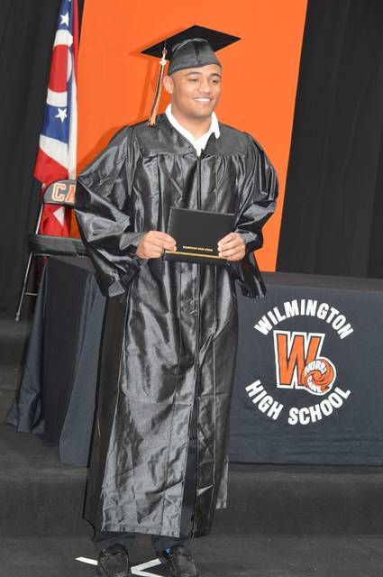 Kile Holland is pleased to display his newly received Wilmington High School diploma during a stage presentation Tuesday for individual 2020 graduates and their parents or legal guardians. At designated times Monday through Wednesday, the traditional Hurricane-style graduation stage was set up and a professional photographer was there to photograph each graduate in cap-and-gown with their diploma and parents.