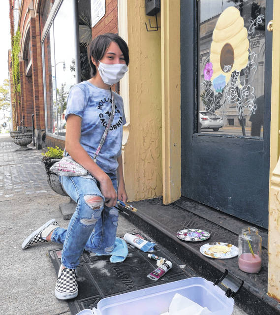 <strong>A WORK IN PROGRESS</strong>: Adryanne Cortes, 13, was acrylic painting the front door at Beehive Custom Framing & Art as part of the Inferno project. Appropriately enough, Cortes painted a beehive, along with colorful flowers and bees.