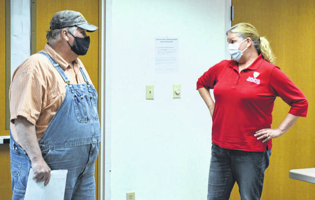 From left, Clinton County Board of Health member Brian Larrick speaks with Clinton County Health Commissioner Pam Bauer after Monday's board meeting.