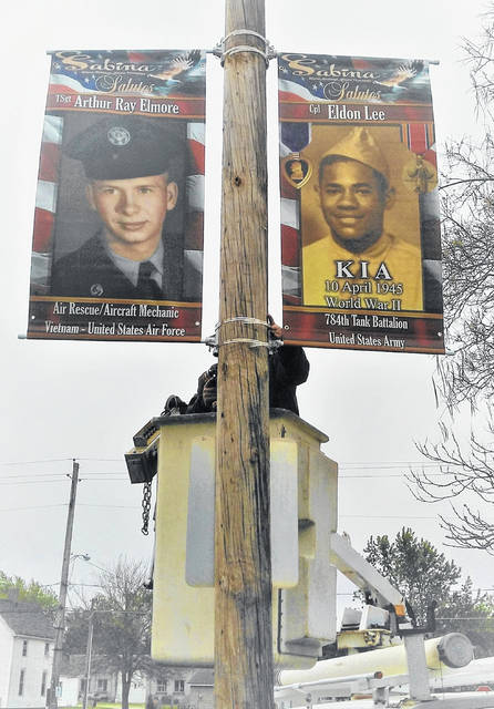 This is the first year for military tribute banners to be hung in Sabina. About two dozen were on display for Memorial Day, and more are expected to be placed as 88 banners have been sold. In the submitted photograph above, the man honored on the right is U.S. Army Cpl. Eldon Lee (784th Tank Battalion), who was killed in action during World War II in April 1945. On the other side is U.S. Air Force TSgt. Arthur Ray Elmore who served during the Vietnam War. Doing the installing is Bryan Floyd in the bucket. Organizer Connie Rice Sears said they are trying to put the banners of family members close to each other.