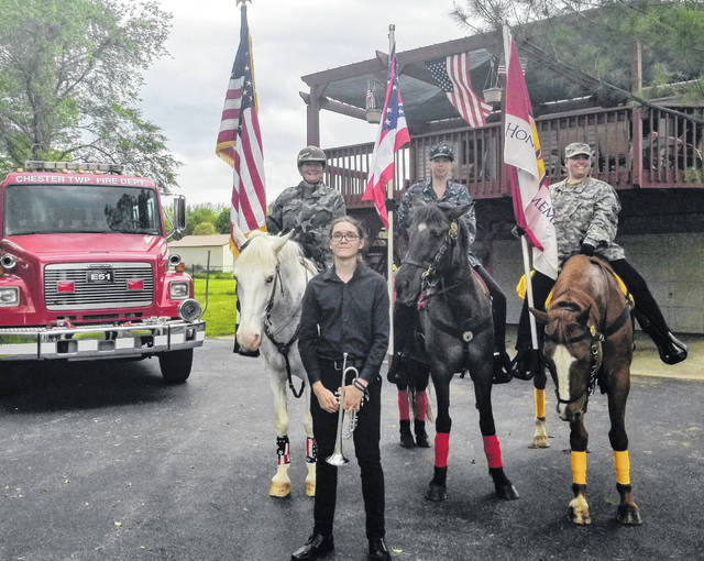 """At 3 p.m. Monday, Memorial Day near the Norton Family home in Clinton County a minute of silence was held and then Adam Norton, standing foreground, played """"Taps"""" on his trumpet. Behind him are members of the 4 Freedom Team mounted honor guard. From left are Judy Kohl on Cricket, Leah Young on Cavalry, and Becky Fitch on Shrek."""