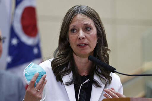 FILE - In this Thursday, Feb. 27, 2020 photo Ohio Department of Health Director Dr. Amy Acton holds up a mask as she gives an update on the state's preparedness and education efforts to limit the potential spread of COVID-19, in Cleveland. Acton, who had a security detail assigned after armed protesters showed up at her home, resigned Wednesday, June 10, 2020. (AP Photo/Tony Dejak)
